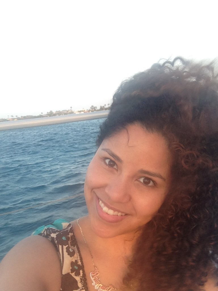 Me, embracing my wild summer curls on a windy boat road in Aruba.